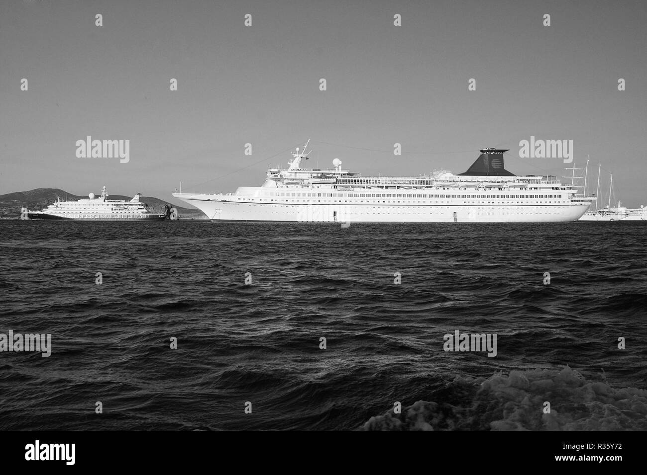 Patmos, Greece - April 19, 2010: passenger ships in blue sea. Cruise ships or liners on sunny sky. Cruising for pleasure voyage. Luxury vacation. Summer vacation and travel. Travelling and wanderlust. - Stock Image