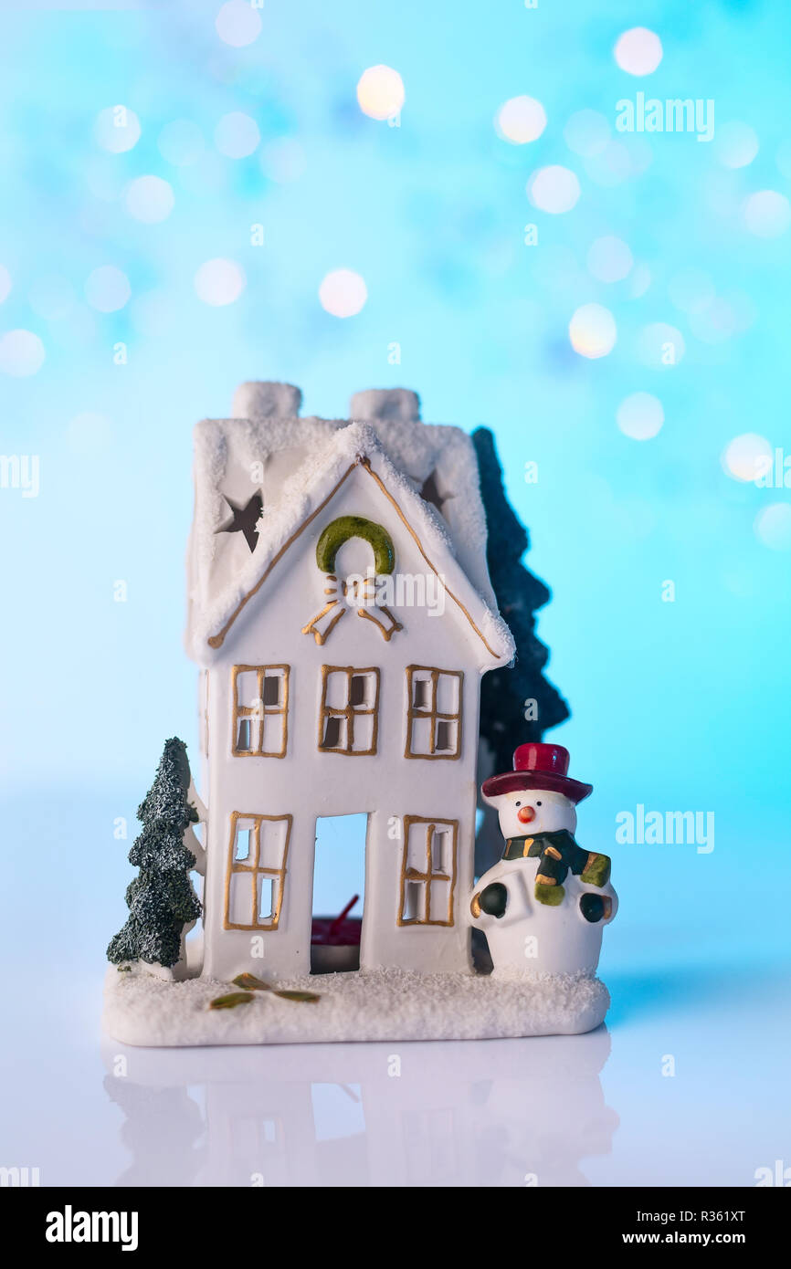 Christmas or New Year snow house, snowman, blue bokeh background with lights - Stock Image