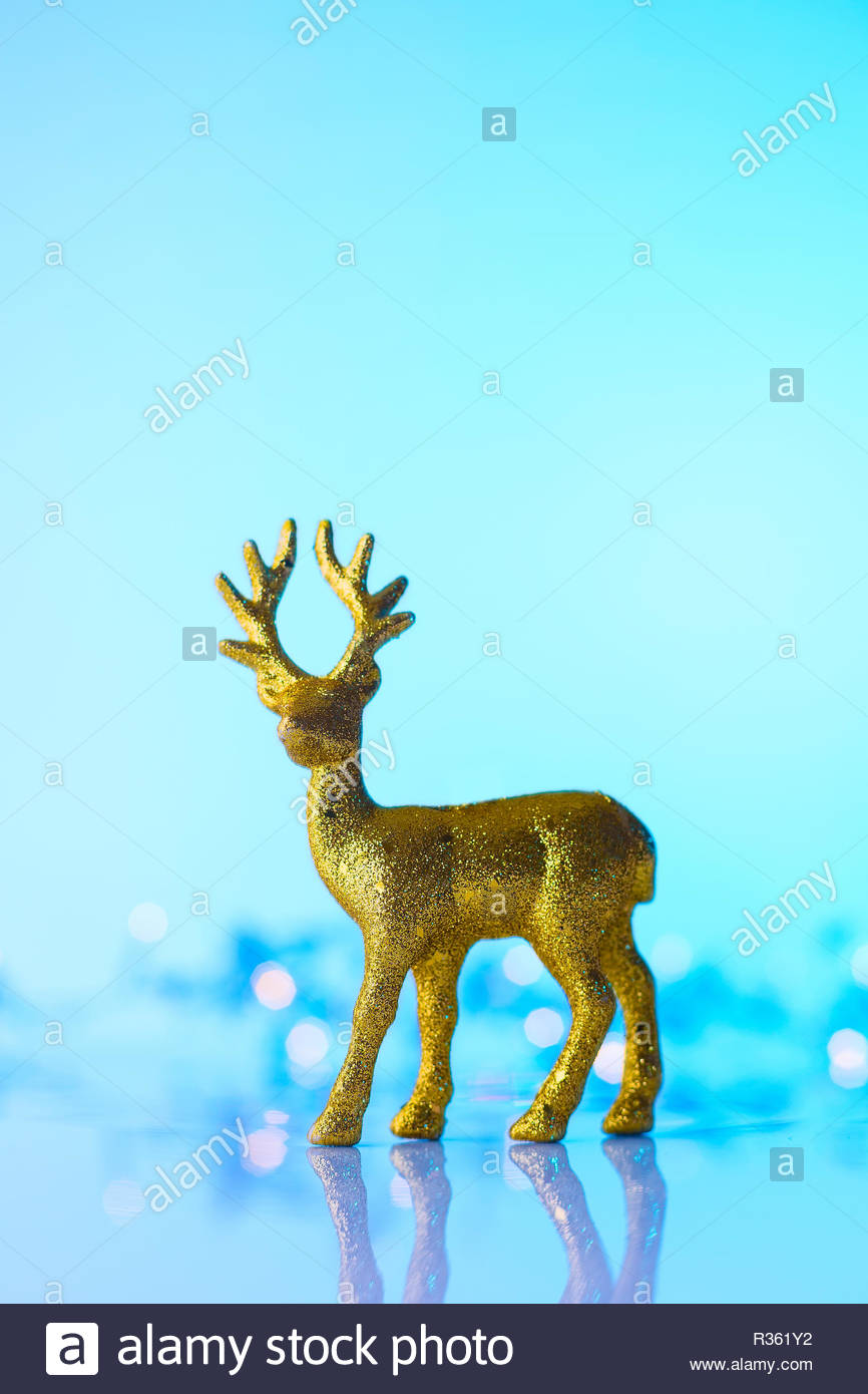 Christmas or New Year golden Reindeer, blue background with lights, copy space - Stock Image