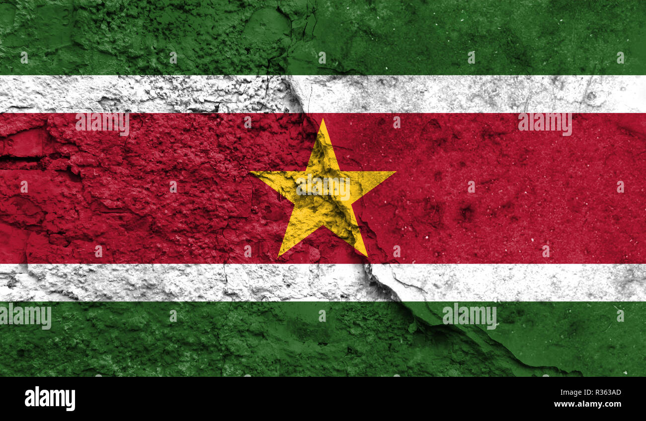 Flag of Suriname close up painted on a cracked wall, concept of armed actions and conflicts in the world - Stock Image