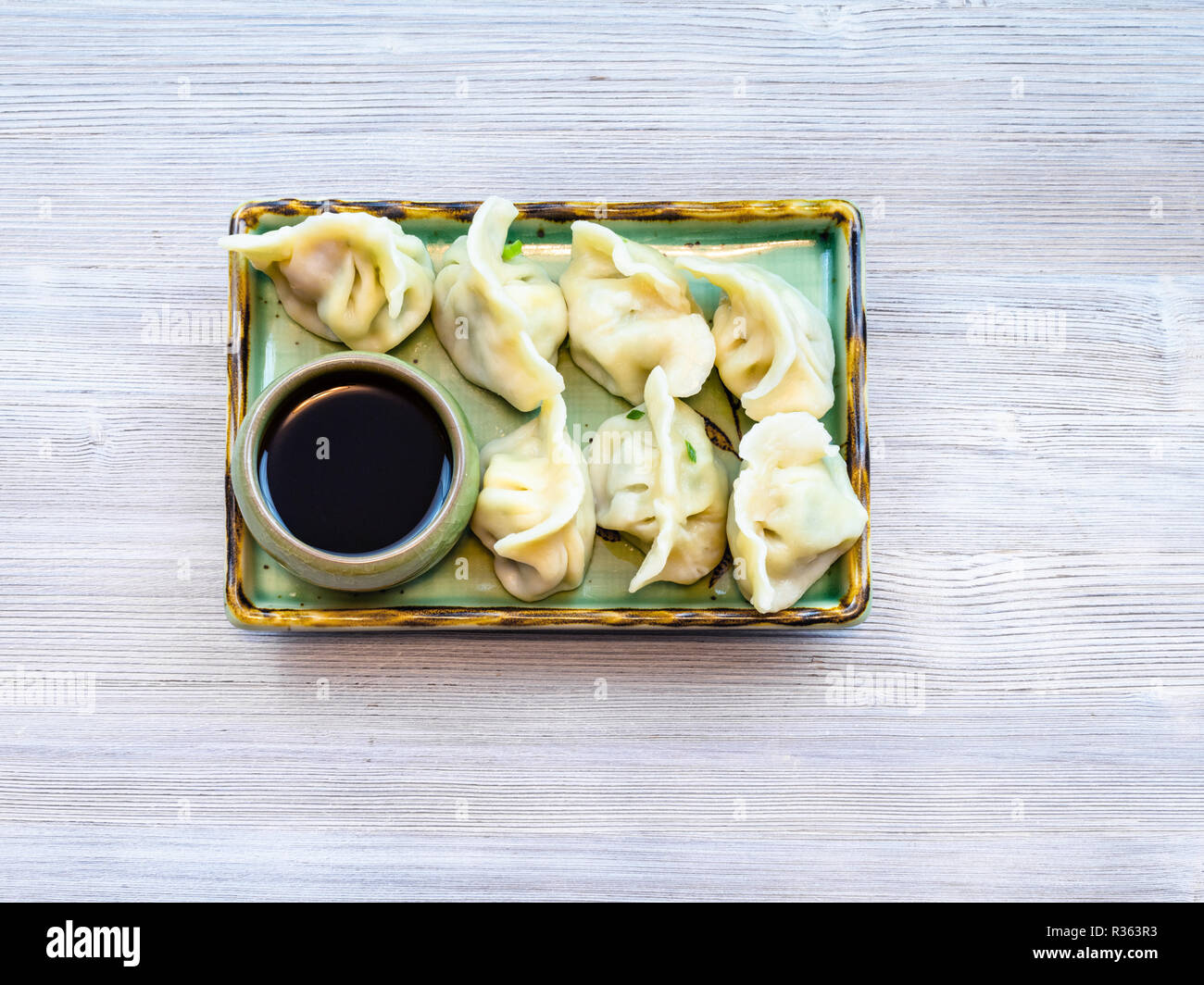 Chinese cuisine dish - top view of served portion of Dumplings with three fillings (shrimp, egg and greens) on green plate on gray table - Stock Image