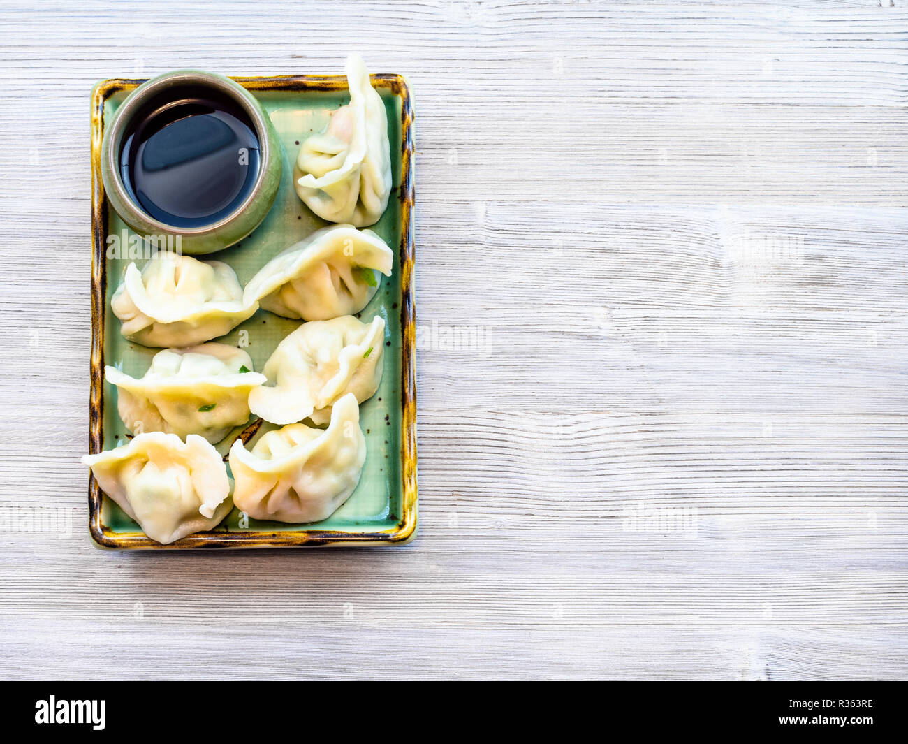 Chinese cuisine dish - served portion of Dumplings with three fillings (shrimp, egg and greens) on green plate on wooden table with copyspace - Stock Image
