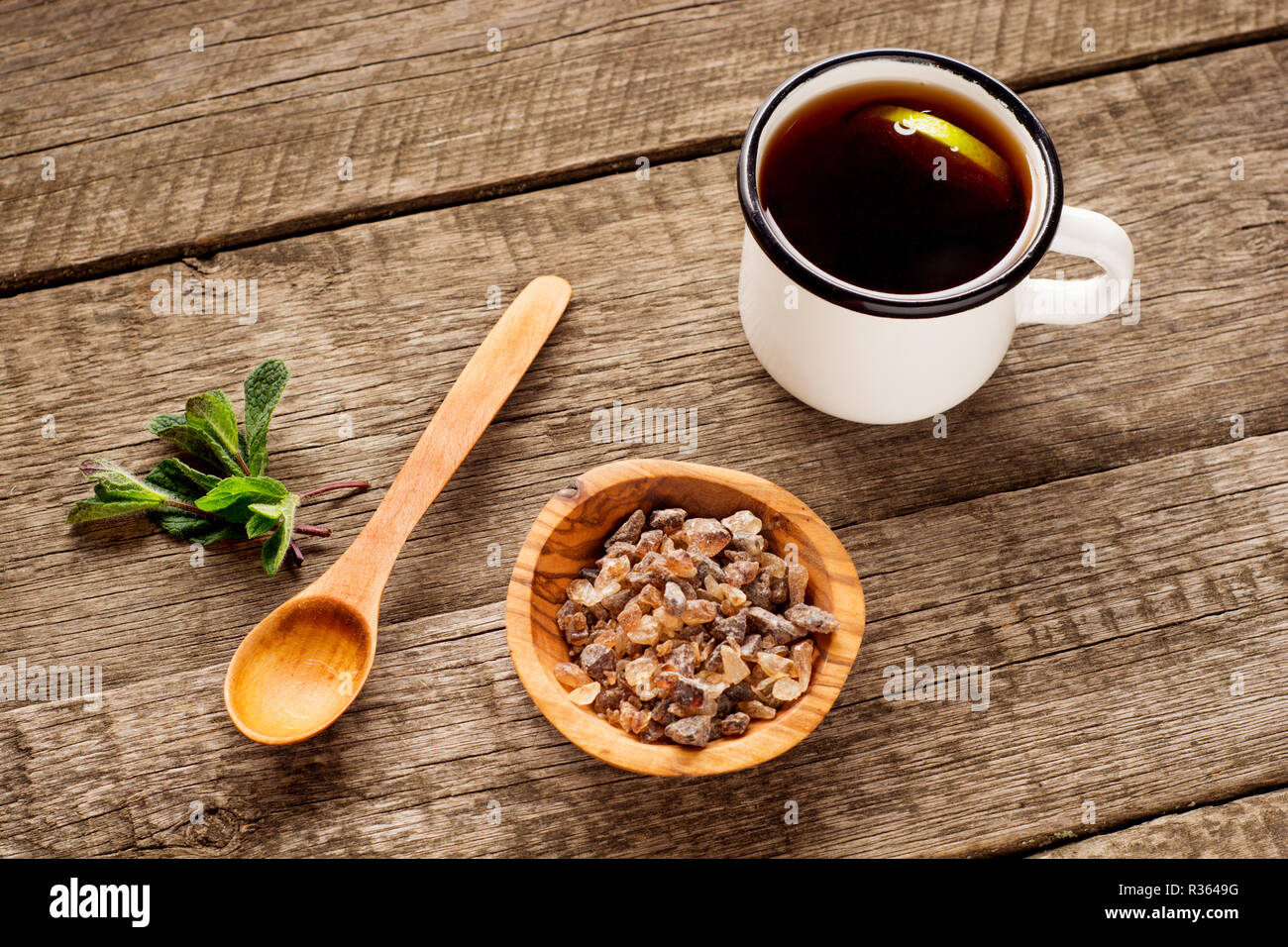 Tea cup with mint leaf and brown sugar in bowl on rustic wooden background. Copy space. Top view. Stock Photo