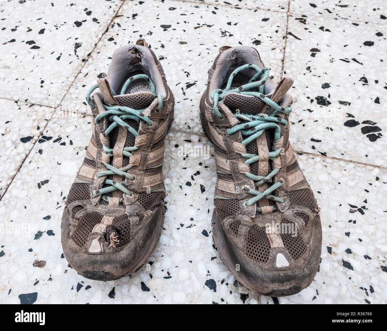 Well worn trainers on textured background - Stock Image