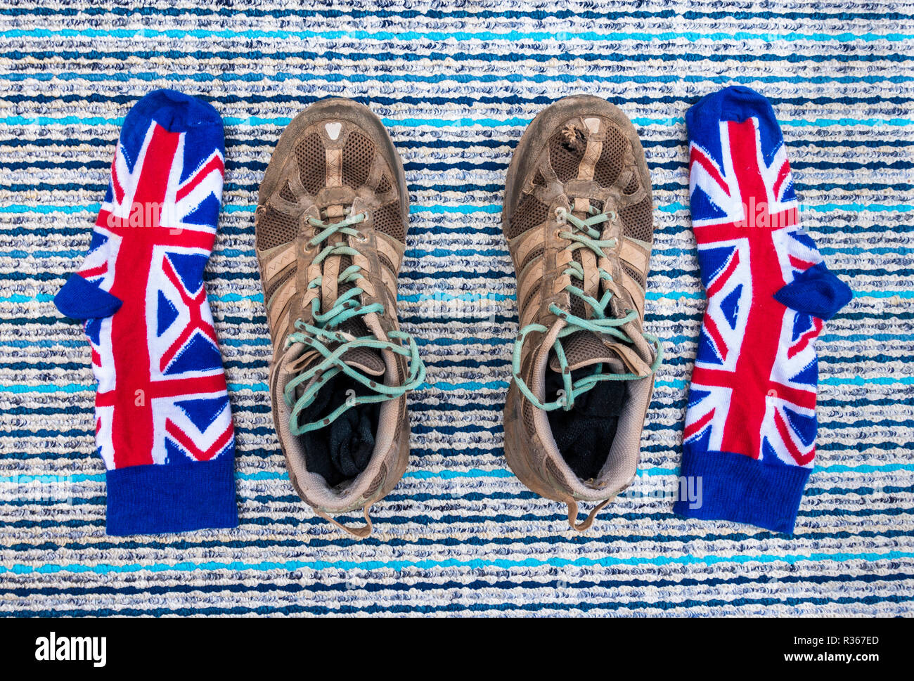 Well worn trainers and union jack socks on textured background - Stock Image