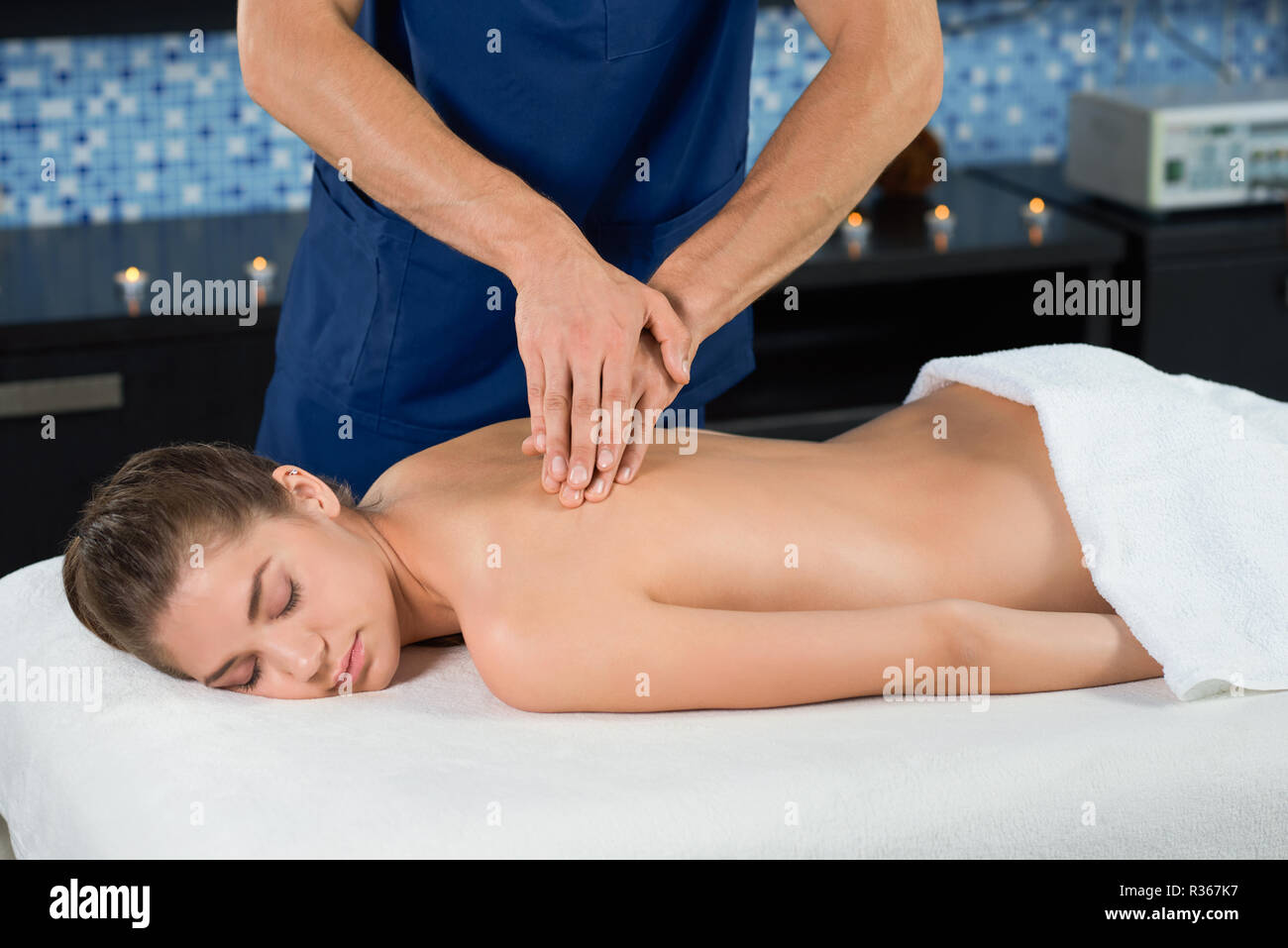 Side view of relaxed woman with closed eyes lyin on couch in spa salon and getting antistressing back massage. Hands of male masseur doing healthy procedure. Concept of calmness and therapy. - Stock Image