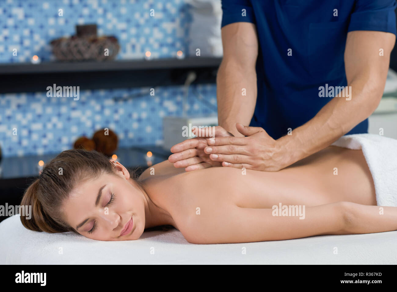 Side view of smiling female client receiving relaxing massage in spa salon. Masseur stretching spine of woman lying on couch with muscular hands. Concept of relaxation and satisfaction. - Stock Image