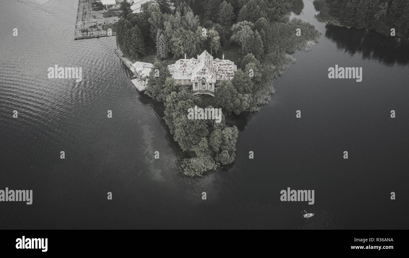 Monochrome drone photography of old abandoned house near a lake. - Stock Image