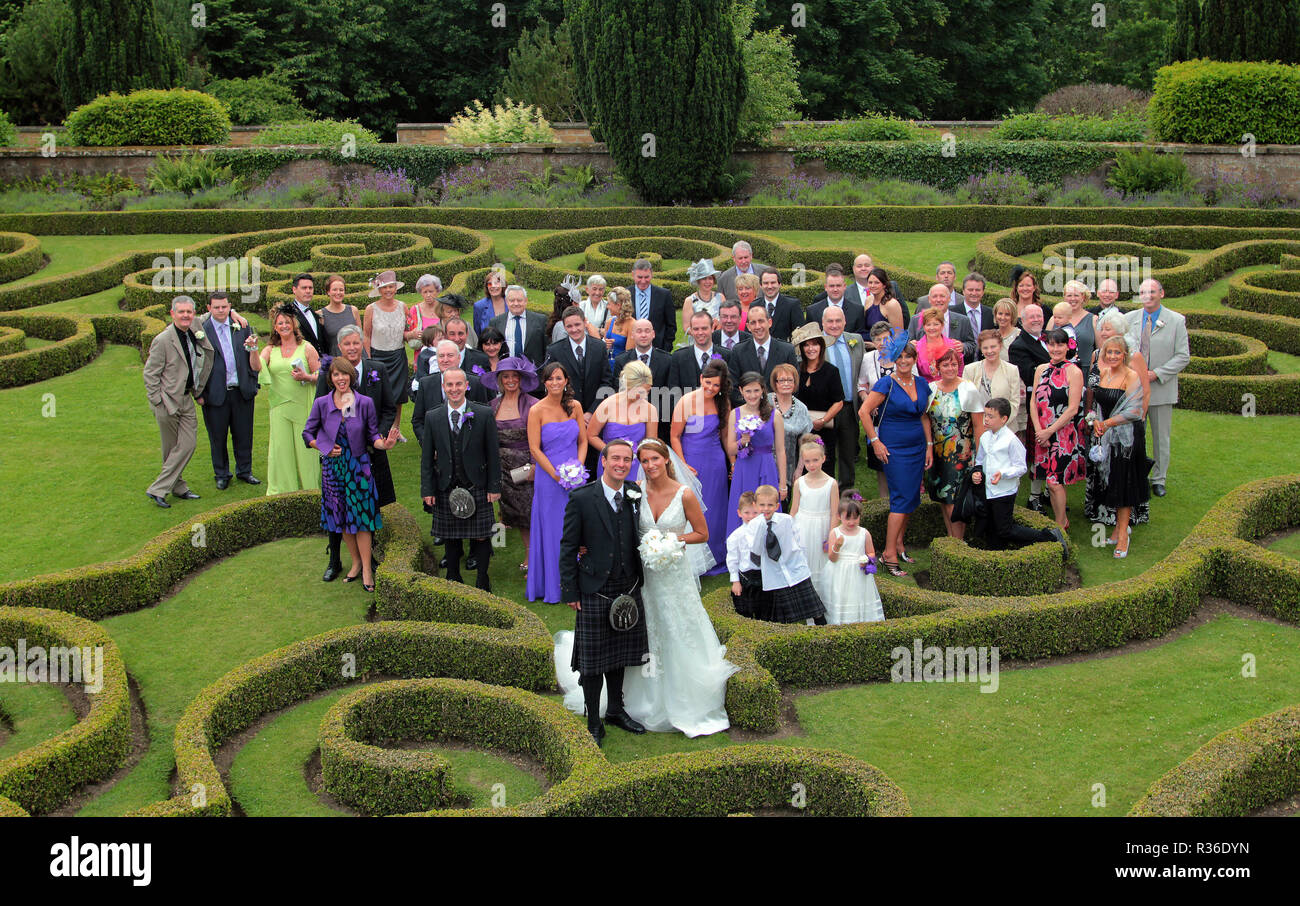 The bride and groom and all of the guests at their wedding pose for a photograph in the garden next to the venue after the ceremony in Scotland. - Stock Image