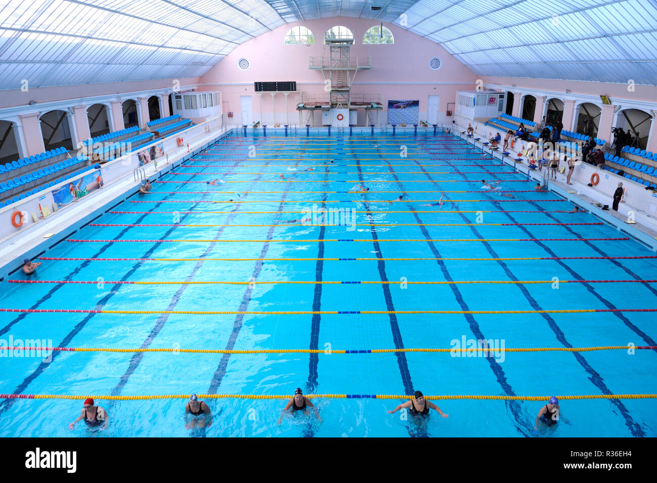 View of indoor swimming pool with people training. Pool of ...