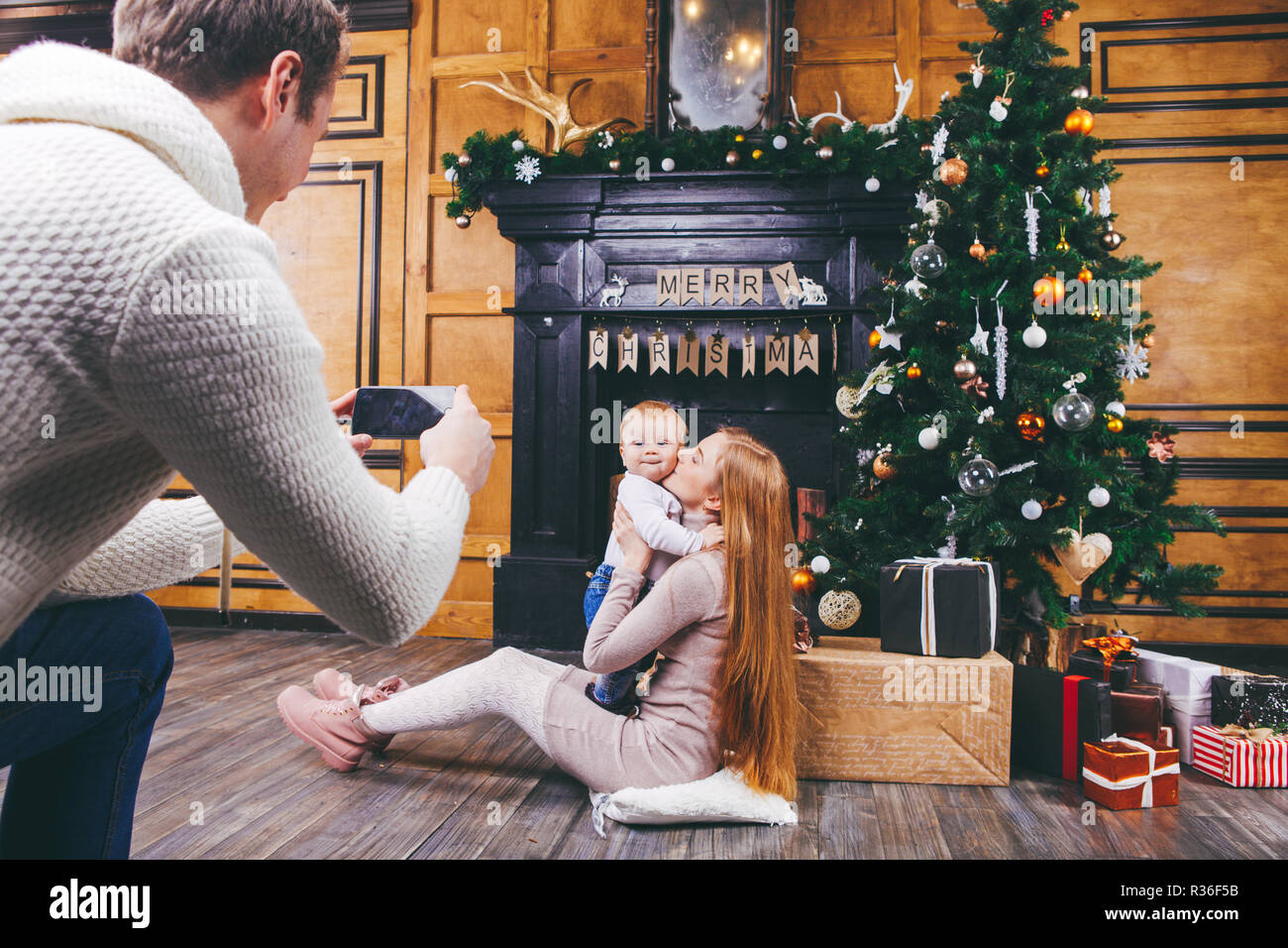 Theme mobile photography, amateur photo video phone. Hands Caucasian man holds uses smartphone makes photo mother and son home near fireplace and Chri - Stock Image