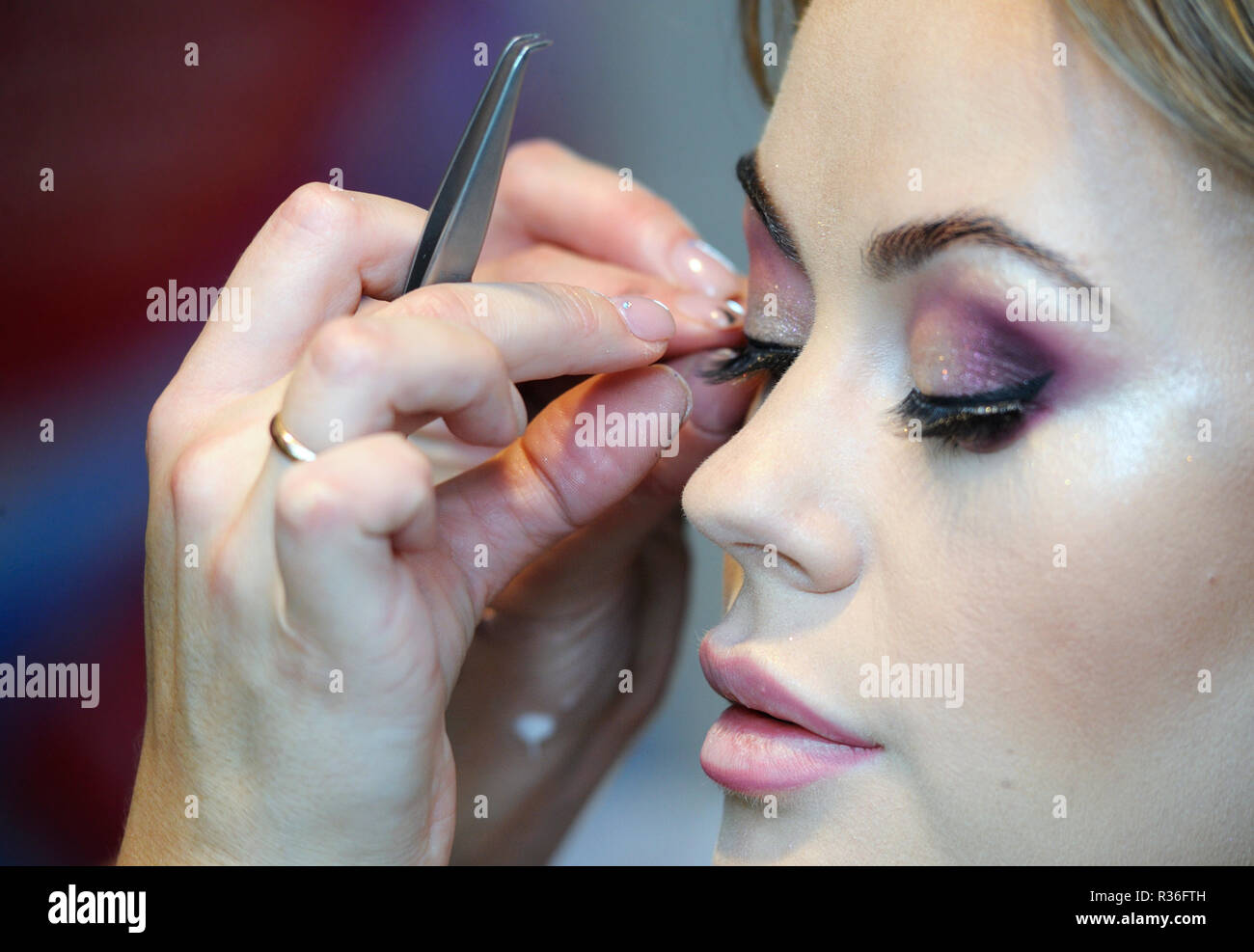 47bdae152a0 At a beauty salon. Make-up artist's fingers fixing false eyelashes on a  female