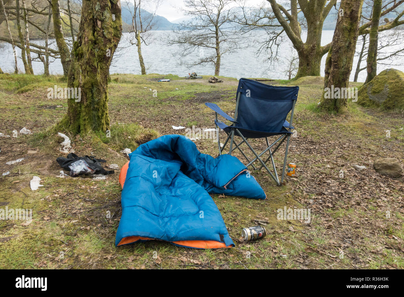 Loch Lomond wild camping litter problems - abandoned campsite - sleeping bag, chairs, rubbish - on east shore just outside camping management zone - Stock Image