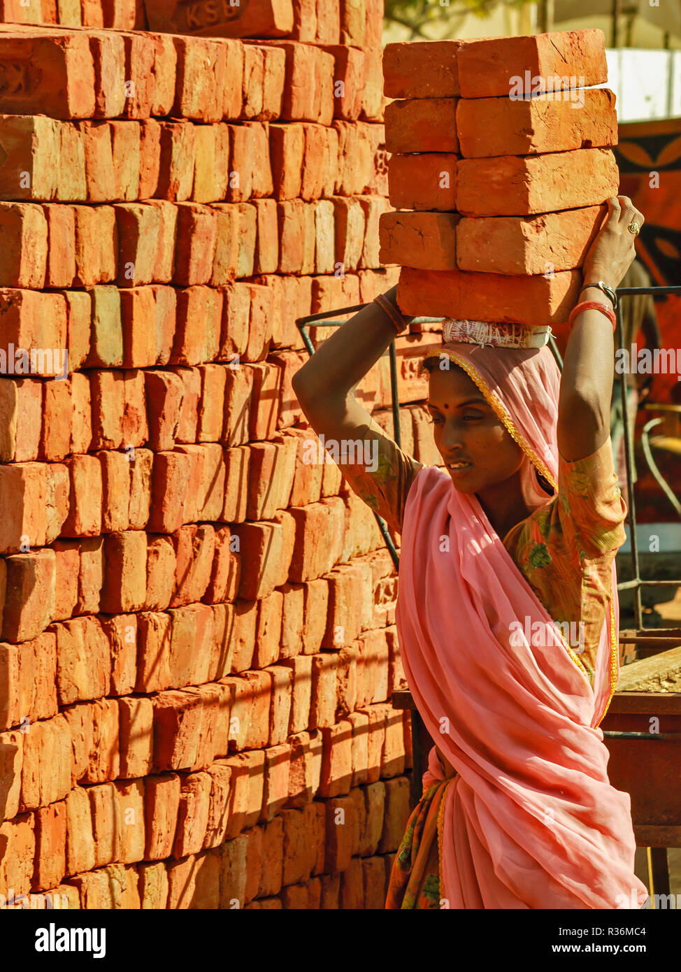 RAJASTHAN INDIA  YOUNG WOMAN CARRYING A LOAD OF HOUSE BRICKS ON HER HEAD - Stock Image