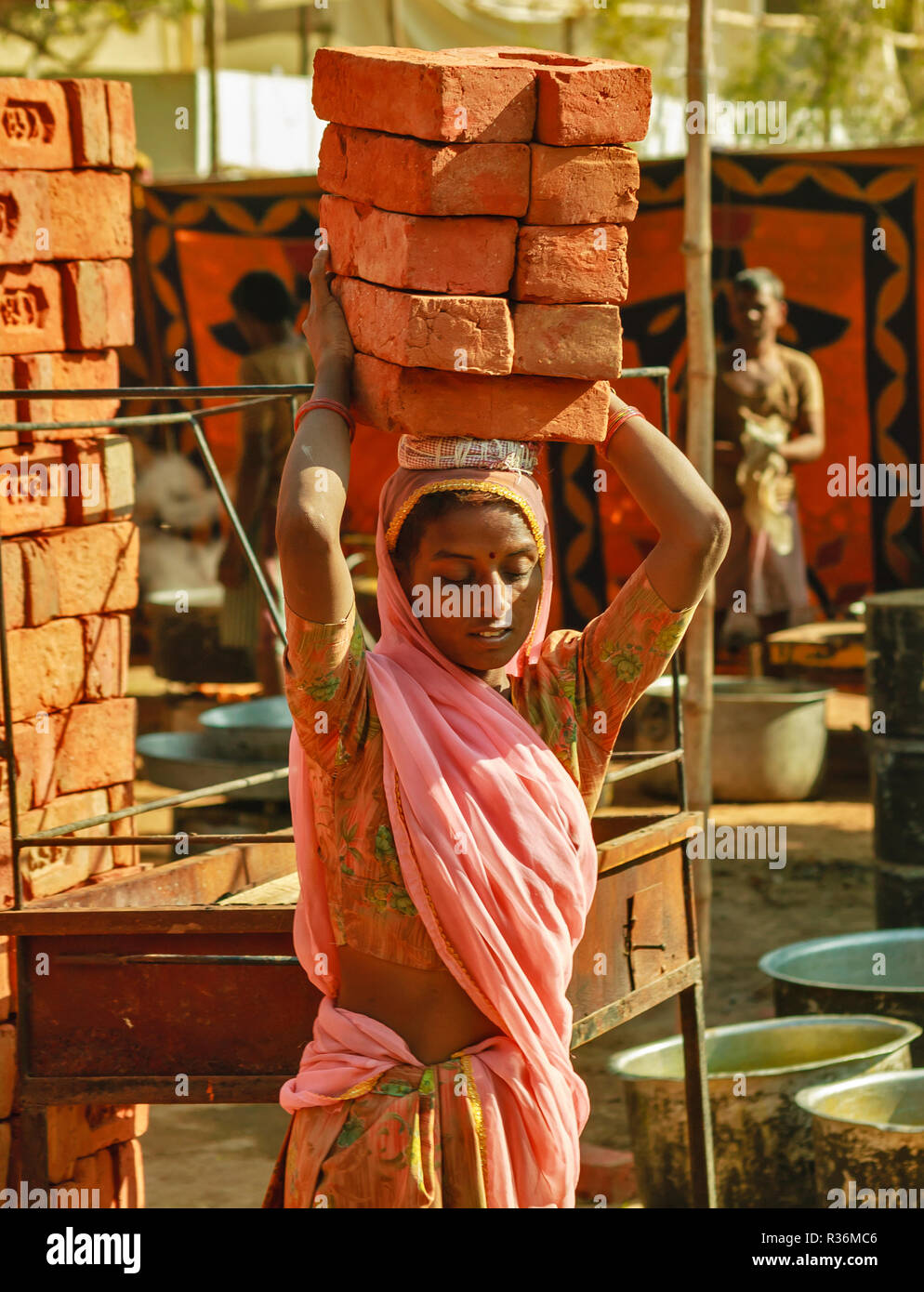 RAJASTHAN INDIA  YOUNG WOMAN CARRYING A LOAD OF TEN HOUSE BRICKS ON HER HEAD - Stock Image