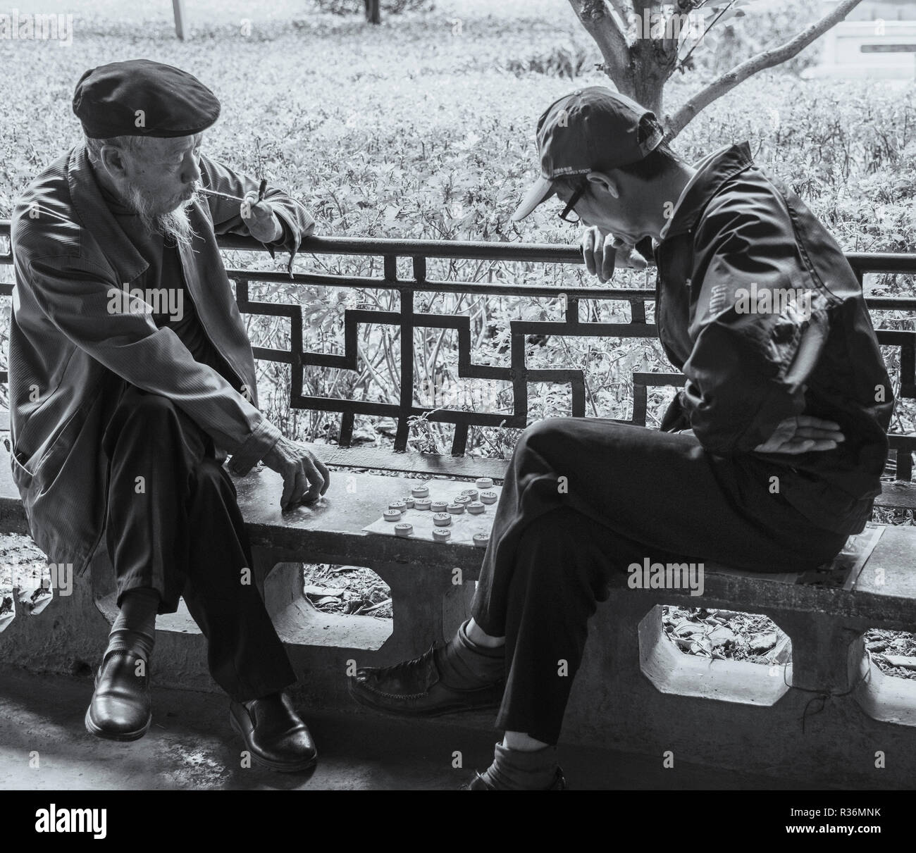 Black and white photo of two elderly chinese gentlemen playing popular game of mah jong in chinese park kunming china