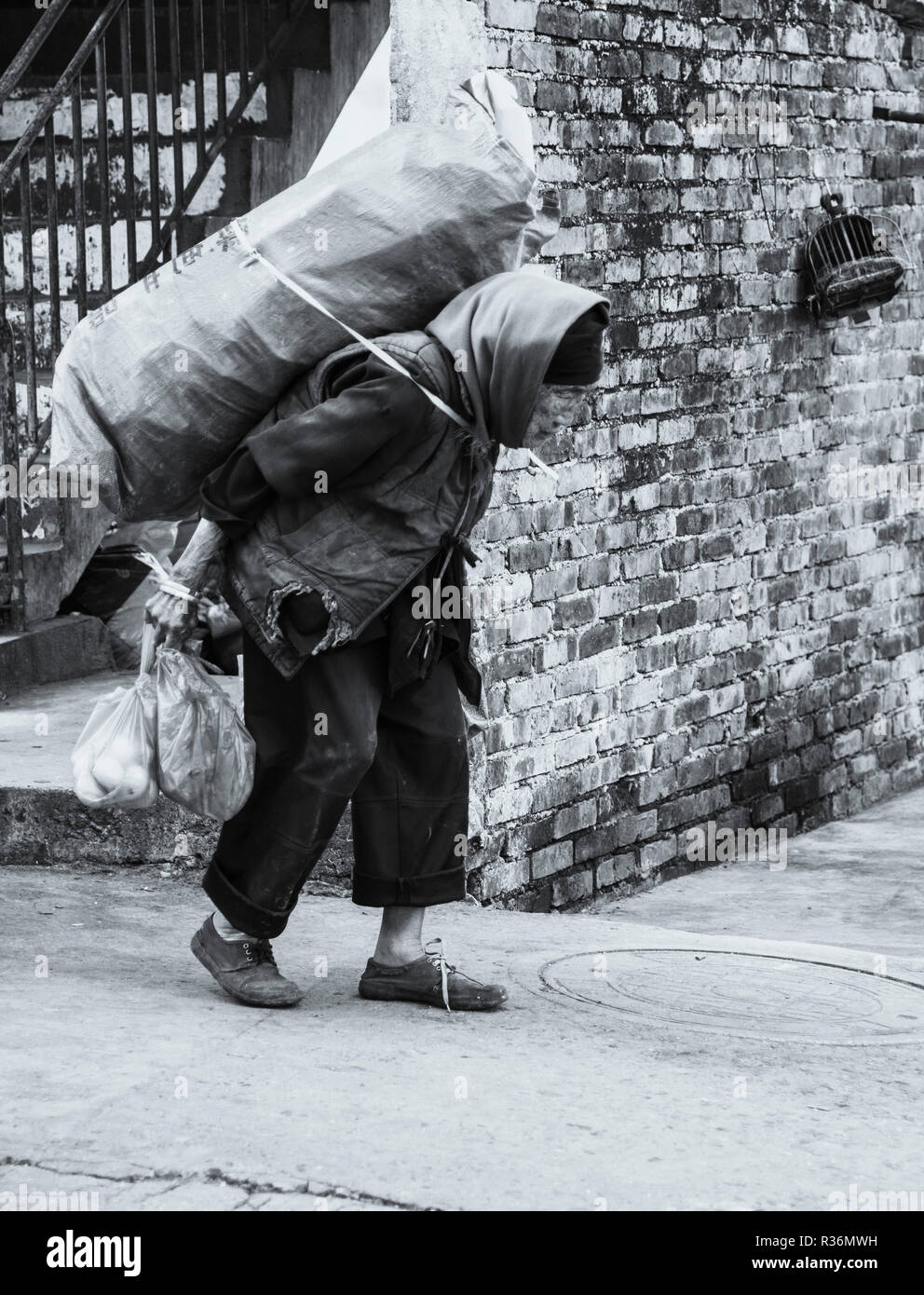 Black and white photo of elderly lady struggling carrying a heavy load in an old chinese town  Jianshui China. - Stock Image