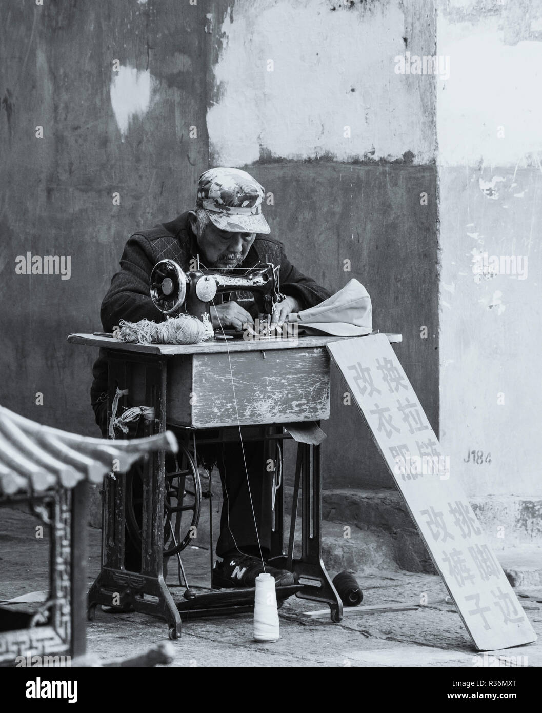 Black and white photo of elderly chinese man earning a living using a sewing machine for clothing alterations in a street in Dali China. - Stock Image