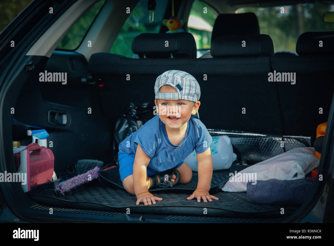 A small child sitting in the trunk of the car plays and laughs - Stock Image