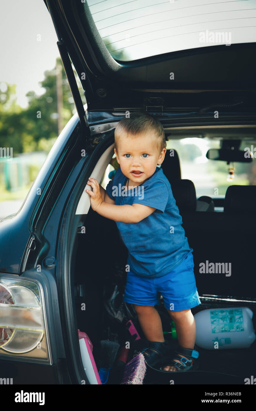 A child stands in the trunk of a car in a blue shirt is playing and smiling - Stock Image