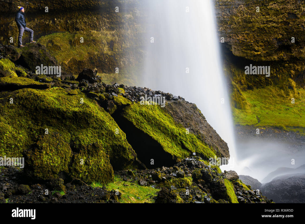 Person standing behind the fascinating Kvernufoss waterfall in Iceland. - Stock Image