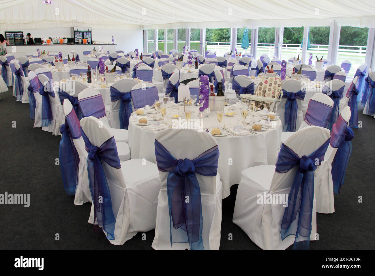 The tables are all laid out, set and ready for the guests inside a huge marquee, for the wedding dinner after the ceremony, at a wedding in Scotland. - Stock Image