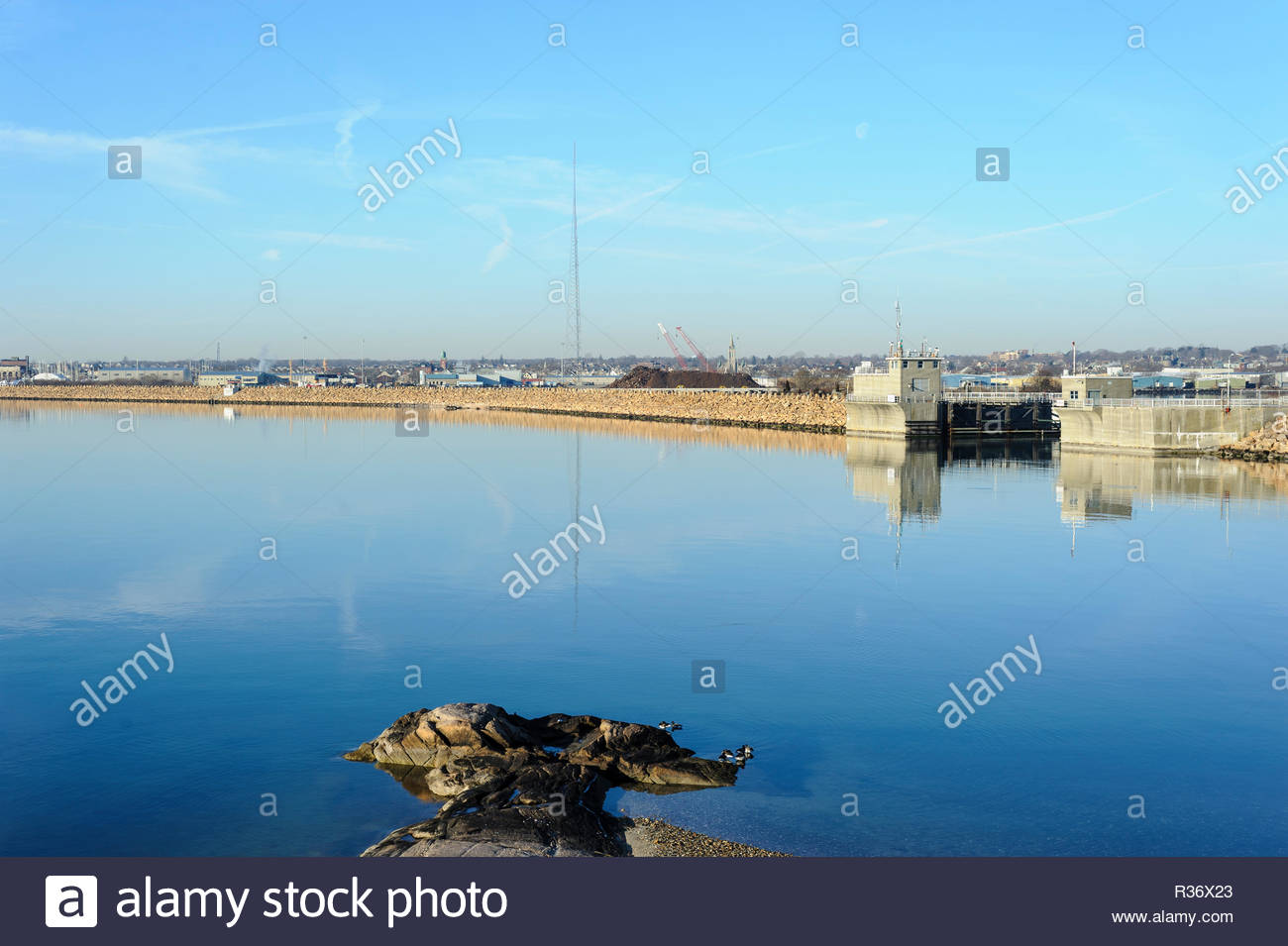 Hurricane barrier on dead calm morning on Acushnet River - Stock Image