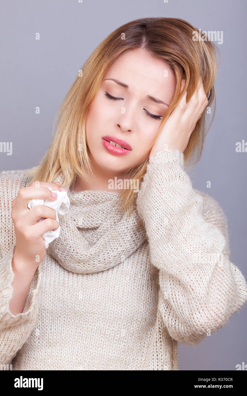 Young sick woman holding her head - Stock Image
