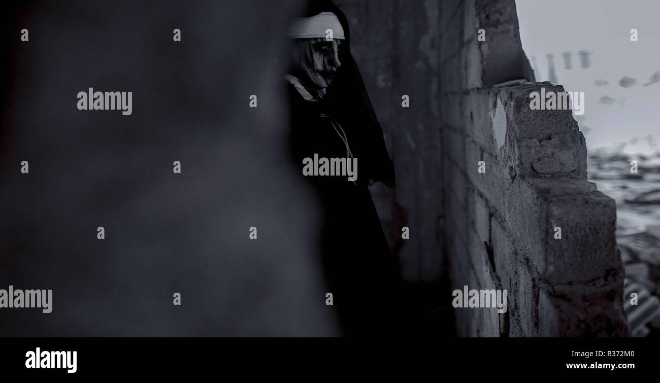 Woman is standing in a darkness dressed in a black hooded cloak in an image of a nun possessed by demons. Cosplay. - Stock Image