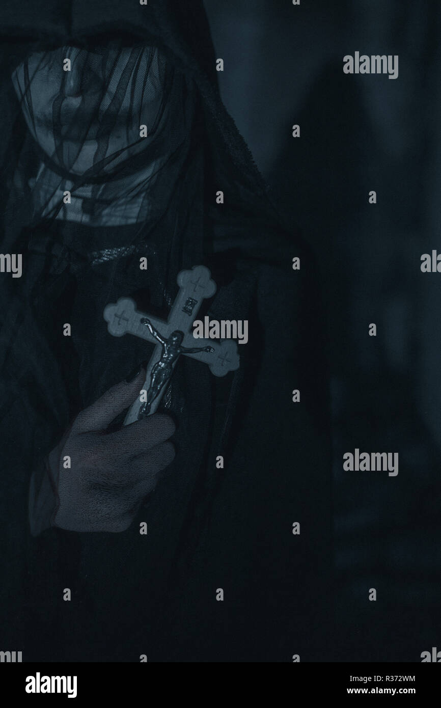 Woman is standing in a darkness with a cross in her hand in a black hooded cloak in an image of a nun possessed by demons. Cosplay. - Stock Image