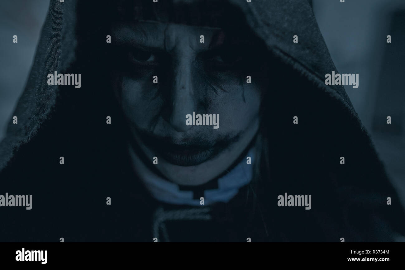 Portrait of standing in a darkness woman dressed in a black hooded cloak in an image of a nun possessed by demons. Cosplay. - Stock Image