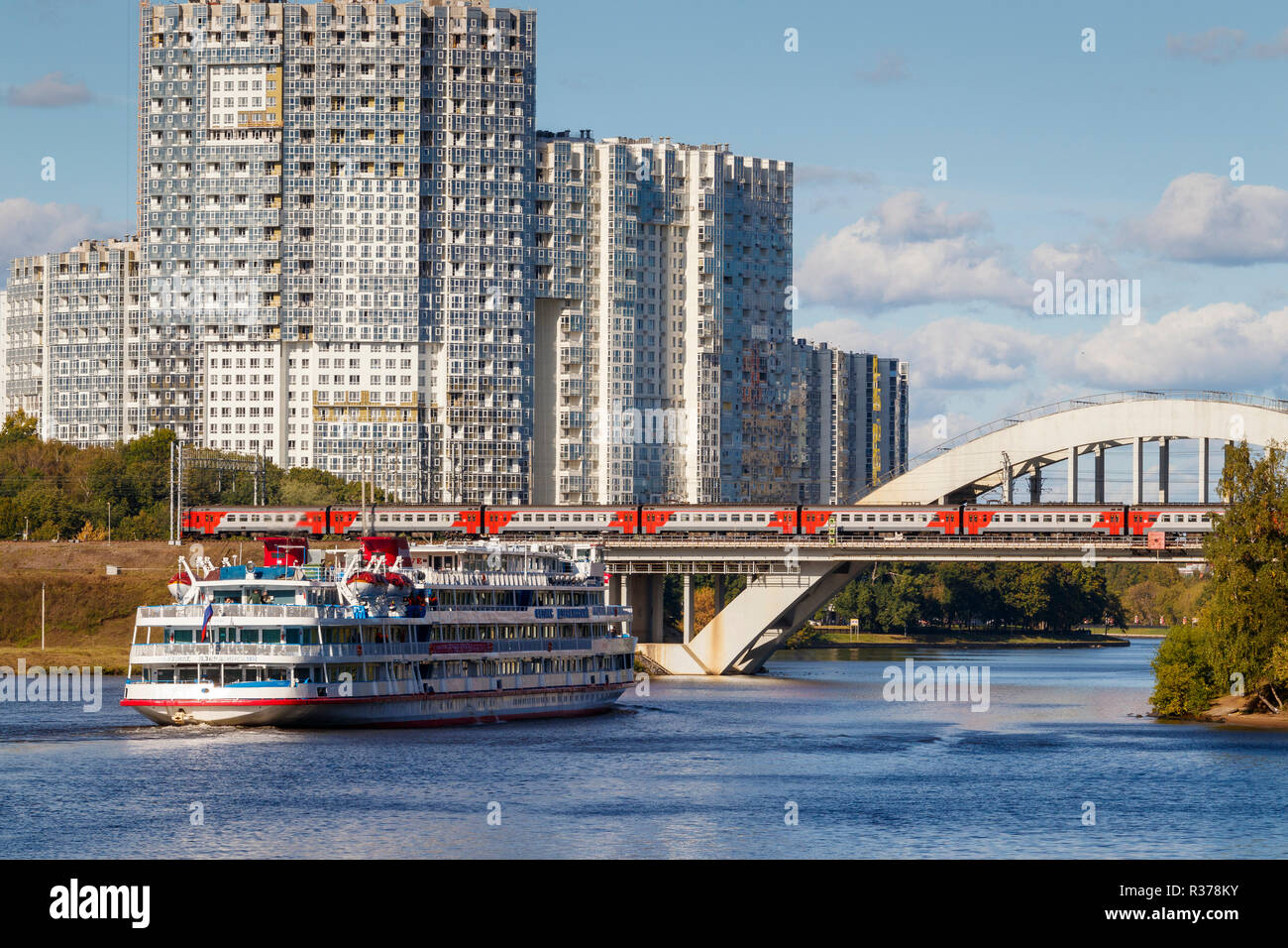 The 1978 Felix Dzerzhinsky cruise ship on the Moscow Canal in central Moscow as it approaches a railway bridge with train crossing, Russia. - Stock Image
