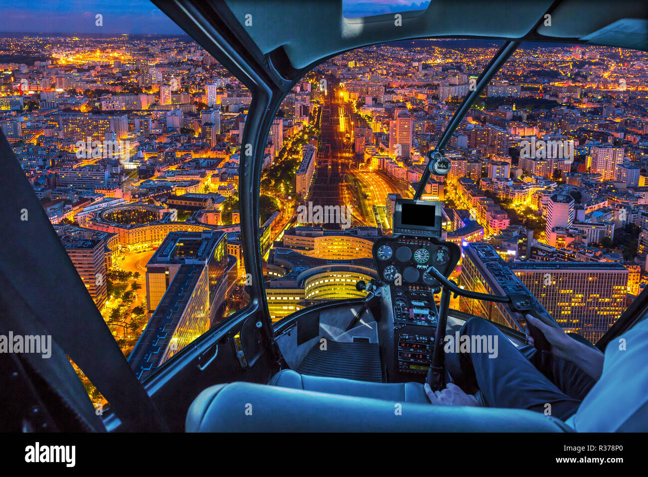 Helicopter cockpit flying on Gare Montparnasse in Paris, French capital, Europe. Scenic flight above Paris urban cityscape. Parisian style architecture of France in Europe. Night scene. Stock Photo