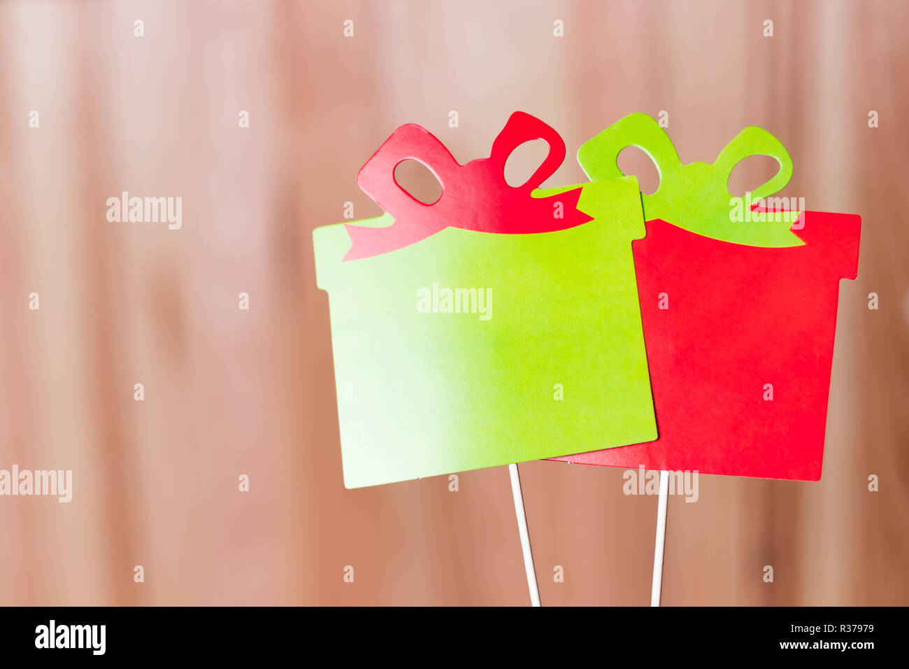 Two colorful christmas presents photo booth props. Red and green. Natural wooden background. - Stock Image