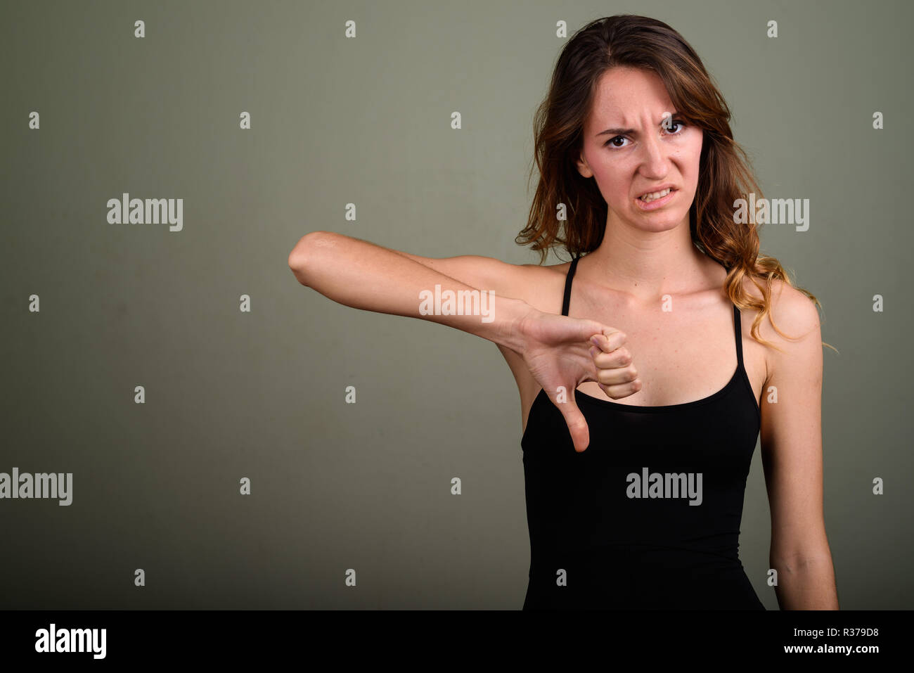 Young beautiful woman wearing sleeveless top against colored bac - Stock Image