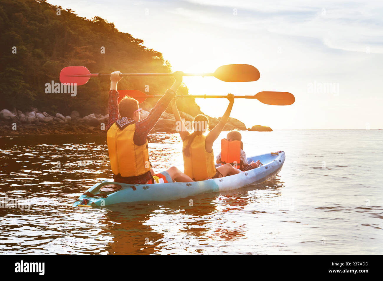 Happy family is walking at sunset sea by kayak or canoe. Active tourism concept Stock Photo