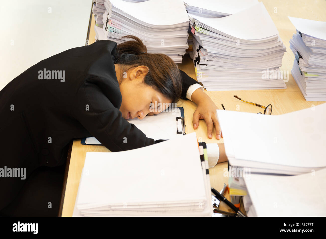 Exhausted woman have lot of work with documents fall asleep on working desk. - Stock Image