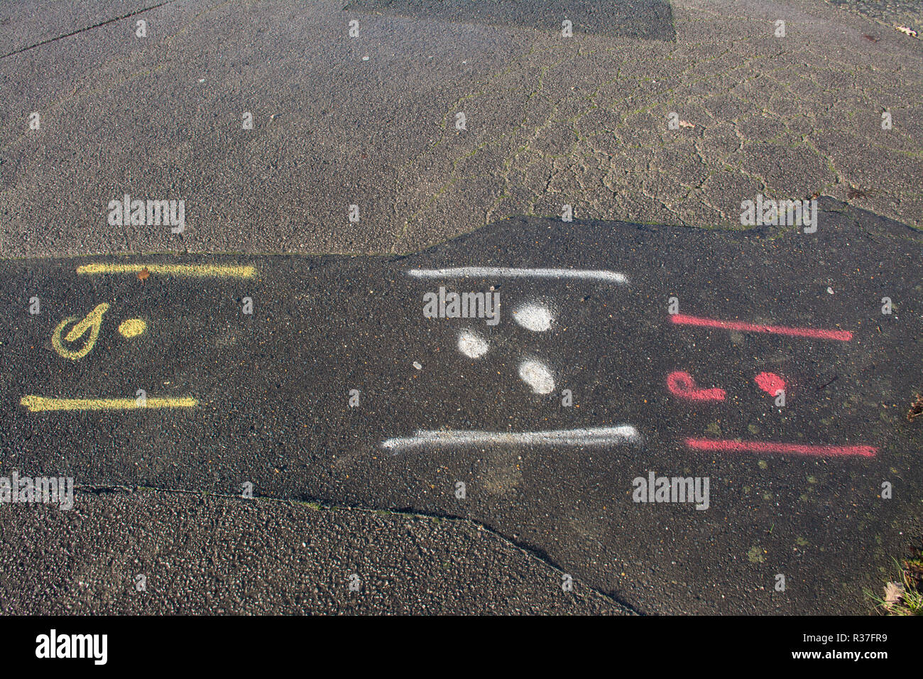 Spray painted markings squiggles on road made by contractors to indicate positioning of water, gas and electric utilities, pipes, cables - Stock Image