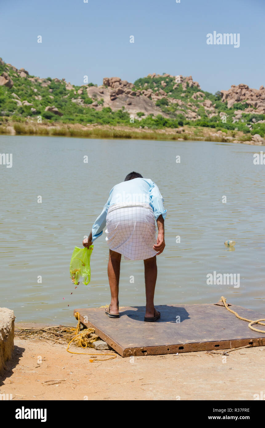 A man puts holy flowers into Tungabhadra River at Talvar Gatta, Anegundi, Karnataka, India - Stock Image