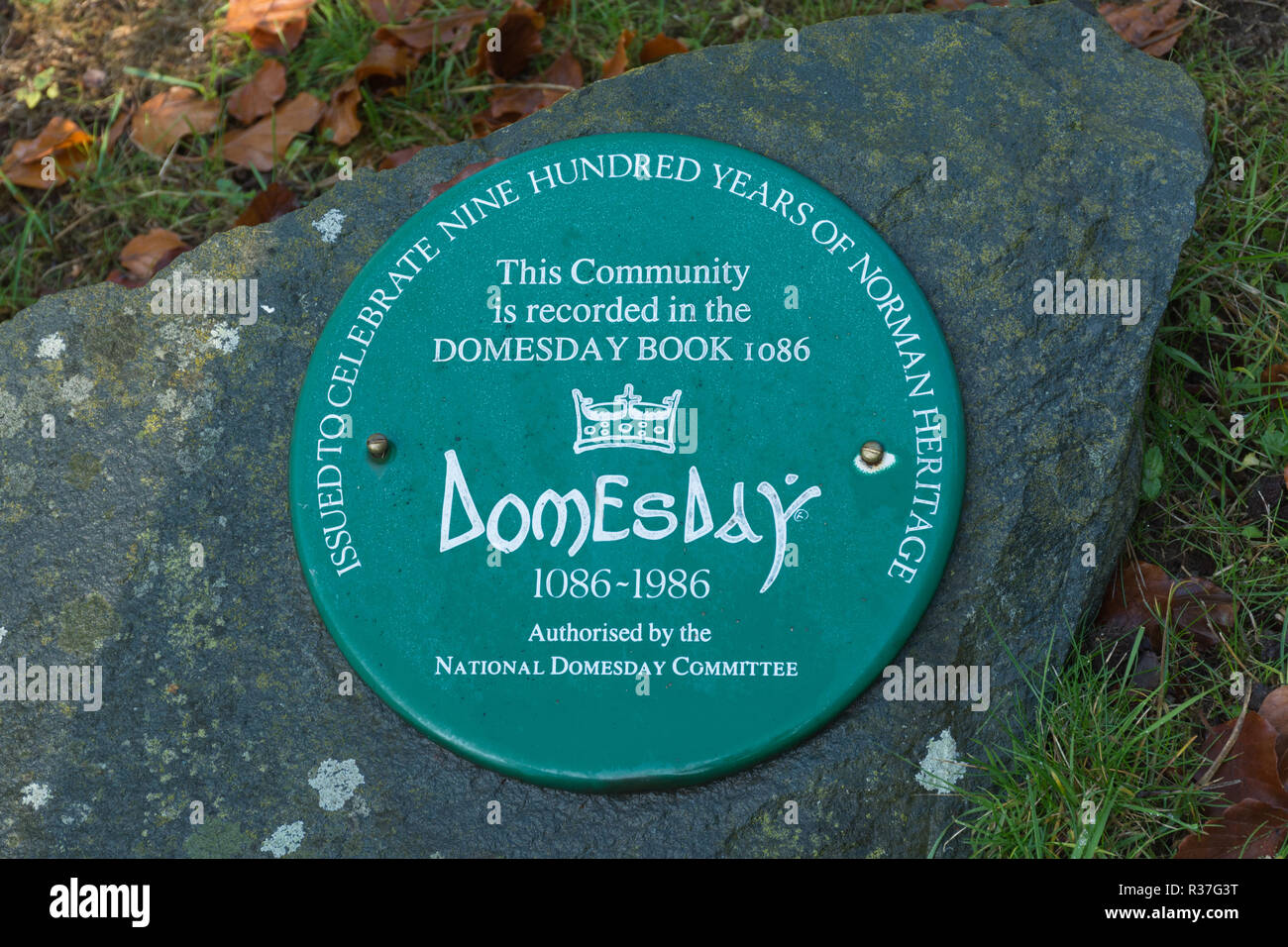 Plaque on a stone in the churchyard in Wanborough, Surrey, UK, saying This community is recorded in the Domesday Book 1086, celebration of 900 years - Stock Image