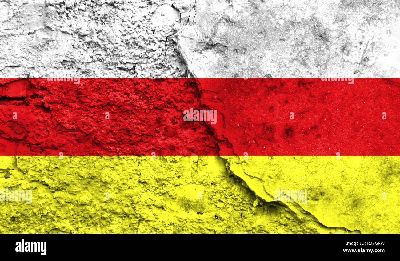 Flag of South Ossetia close up painted on a cracked wall, concept of armed actions and conflicts in the world - Stock Image