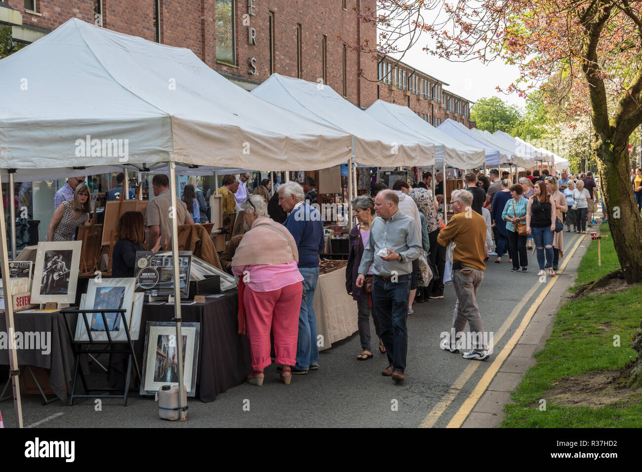 Shoppers visiting the outdoor artisan market in Wilmslow Cheshire,  The market takes place in the town centre.  A sunny spring day - Stock Image