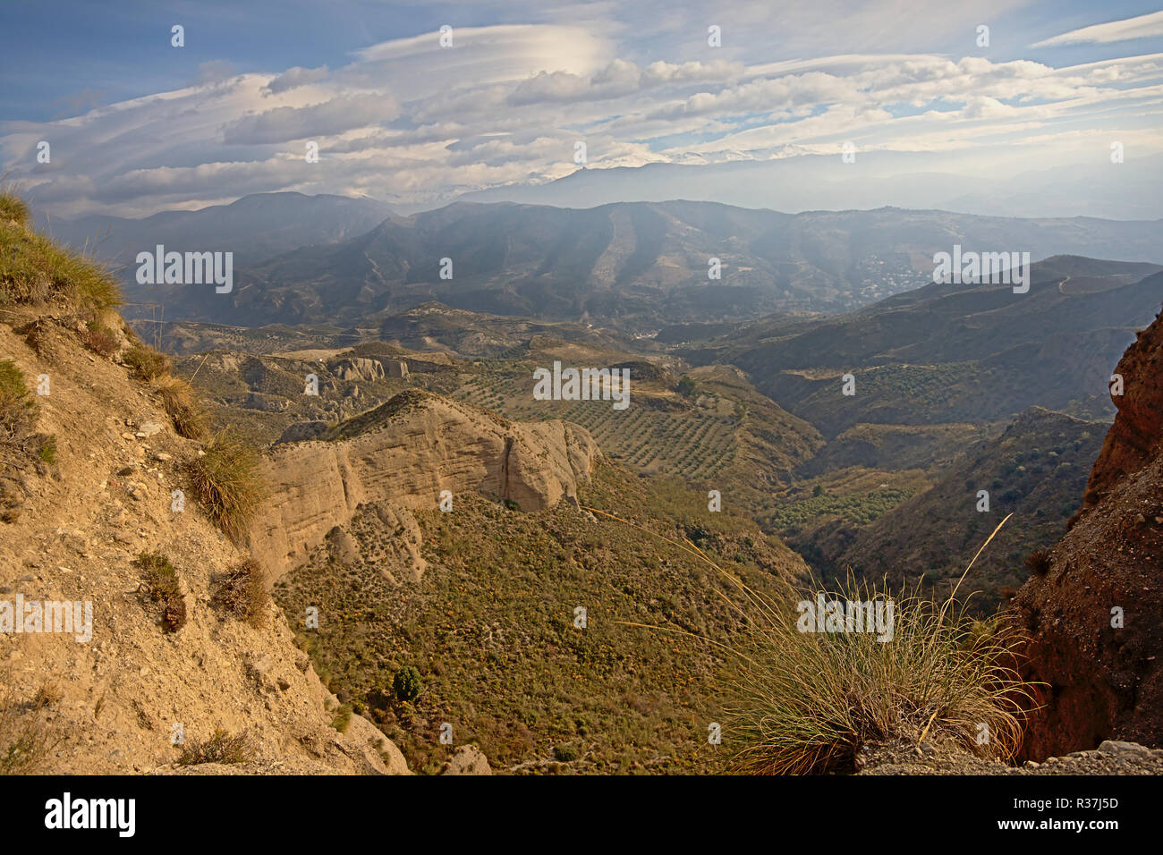 Cliffs of Sierra Nevada mountains on a sunny day with soft clouds, Andalusia, Spain - Stock Image