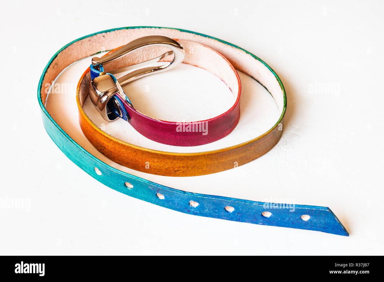 narrow varicoloured leather belt on white background - Stock Image