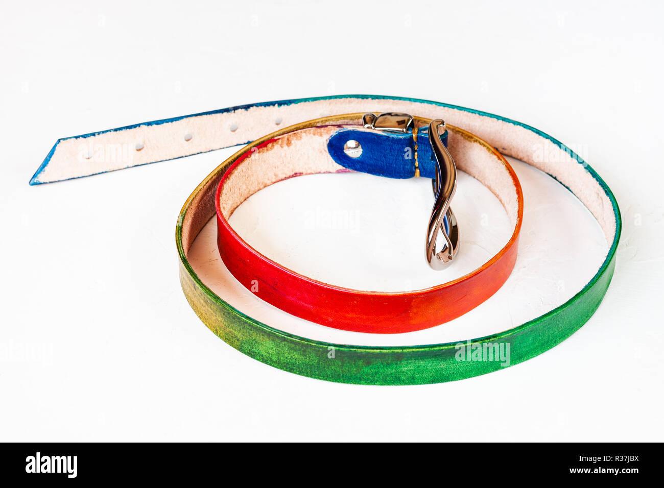 handmade rainbow coloured leather belt on white background - Stock Image
