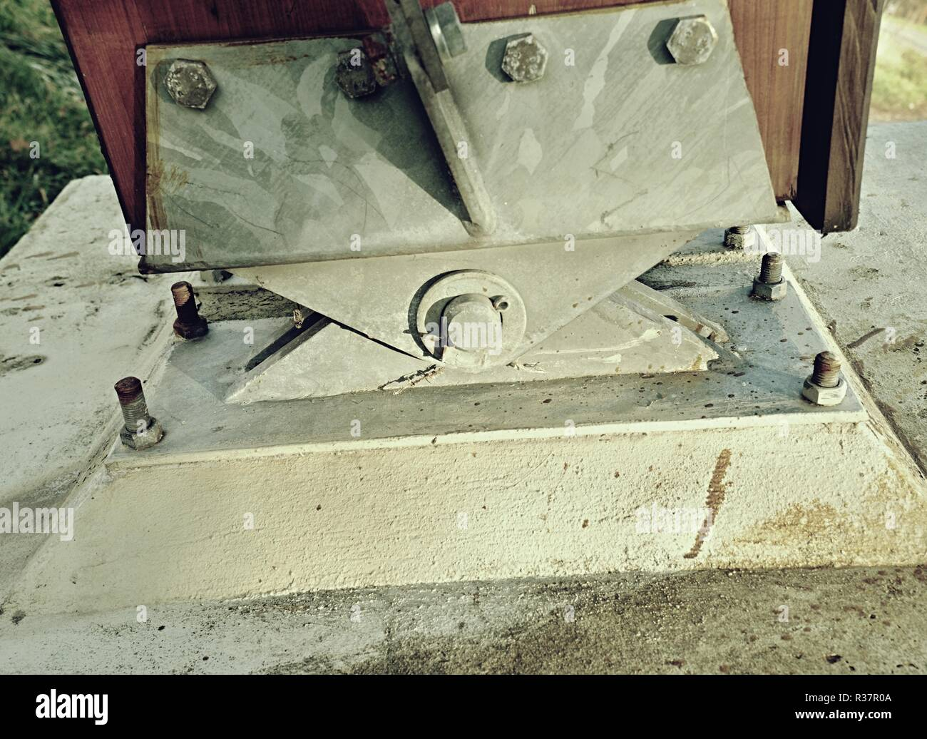 Steel tie joint with swing  beam and anchored into concrete. Modern foot bridge base. Stock Photo