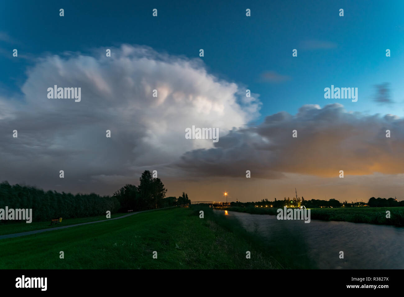 An autumn thunderstorm moves over the dutch countryside at blue hour - Stock Image