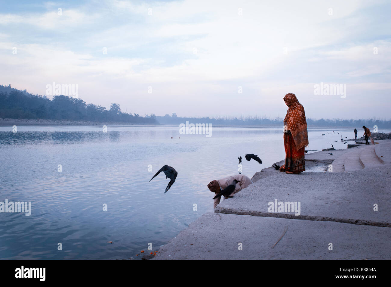 Pelgrims at early morning hour alongside the holy Ganges river. Rishikesh, India - Stock Image
