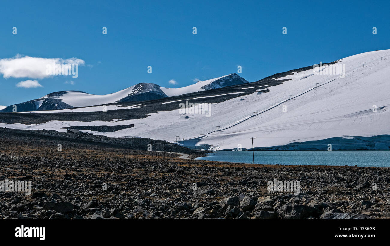 Galdhøpiggen (2469m) far right is the highest mountain in Scandinavia and an imposing backdrop to skiing activities on the Vesljuv glacier on Juvatnet - Stock Image