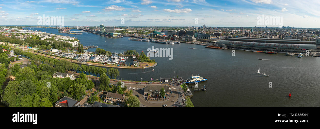 AMSTERDAM, THE NETHERLANDS - June 04, 2017: Aerial view of Amsterdam city center harbor and IJ river with ferry and central train station in summer. - Stock Image